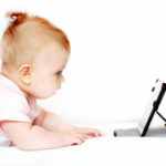 Small baby using tablet pc on white